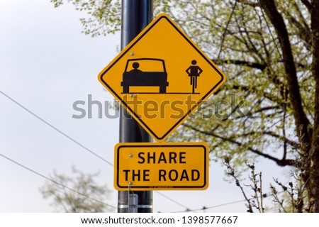 Closeup of a Share the Road sign with car and bicycle pictograms, on a lamp post #1398577667