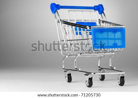 closeup of a shopping cart on gray background