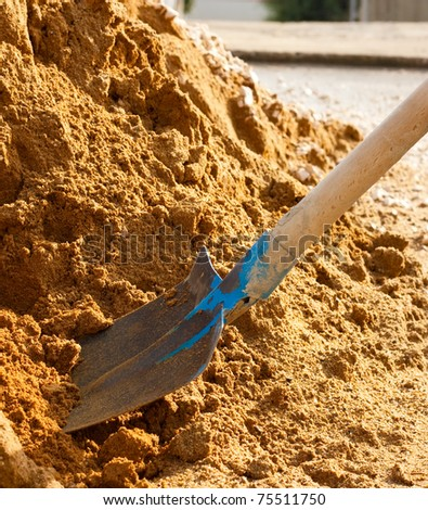 Closeup of a shovel digging into pile of building sand