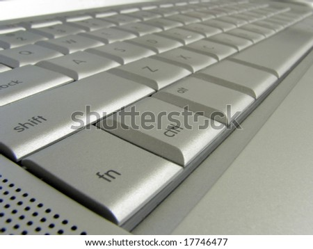 Closeup of a silver keyboard showing some symbols and letters.