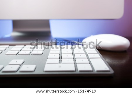Closeup of a silver keyboard with white buttons and a white mouse and screen in the back.