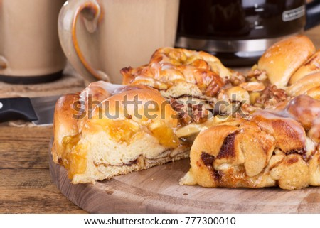 Closeup of a slice of apple pecan sweet bread on a wooden platter #777300010