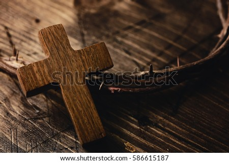 closeup of a small wooden cross and a depiction of the crown of thorns of Jesus Christ on a wooden surface