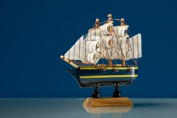 Closeup of a small wooden model of a sailing ship, blue background