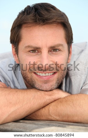 Closeup of a smiling man with stubble resting his head on his arms