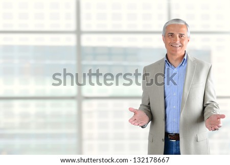 Closeup of a smiling middle aged businessman gesturing with both hand. Man is standing in front of a large modern office building window. Horizontal Format.