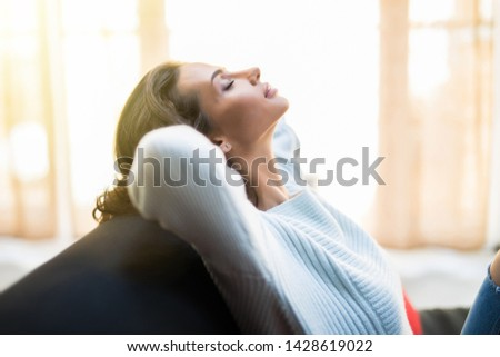 Closeup of a smiling young woman lying on couch #1428619022