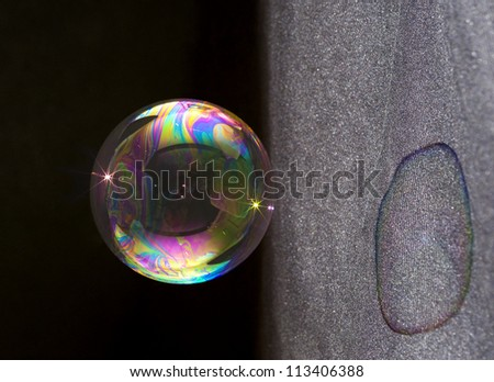 Closeup of a soap bubble and its colorful shadow.