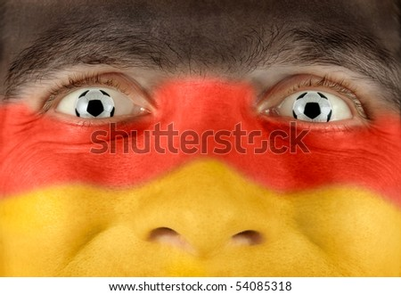 Closeup of a soccer fan with the German colors all over his face and balls as eyes