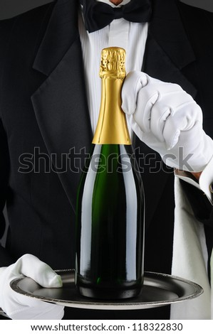 Closeup of a sommelier holding a champagne bottle on a serving tray in front of his torso. Man is wearing a tuxedo and is unrecognizable. Vertical Format.
