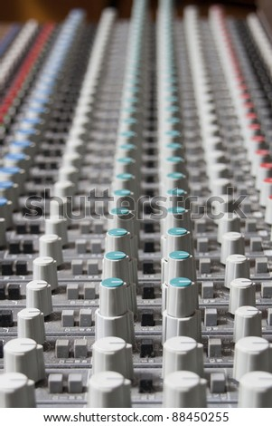 Closeup of a sound board mixer with shallow depth of field
