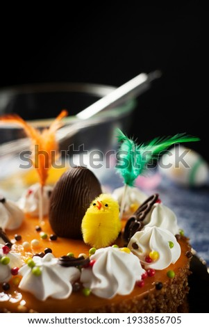 closeup of a spanish mona de pascua, a cake eaten on Easter Monday, ornamented with a plush chick, a chocolate egg and feathers of different colors, on a table Foto stock ©