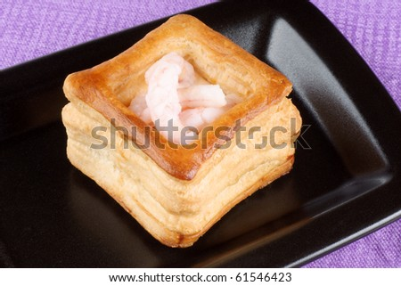 Closeup of a squared vol-au-vent stuffed with small boiled shrimps on a black plate