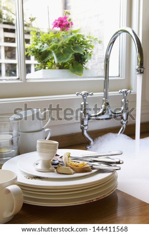 Closeup Of A Stack Of Dirty Dishes And Silverware By Sink With Running Water Below Window With Flower