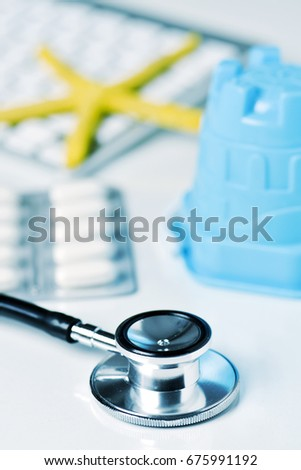 closeup of a stethoscope, a blue beach pail, some pills and a yellow starfish on a computer keyboard, on a doctors office, depicting the medical aid in summer concept