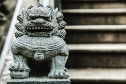 Closeup of a stone lion sculpture in front of stone steps