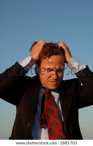 Closeup of a stressed business guy or salesman, portrait view, pulling his hair.