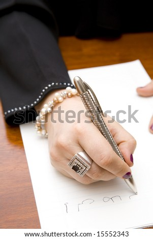 Closeup of a stylish woman writing a note in Arabic