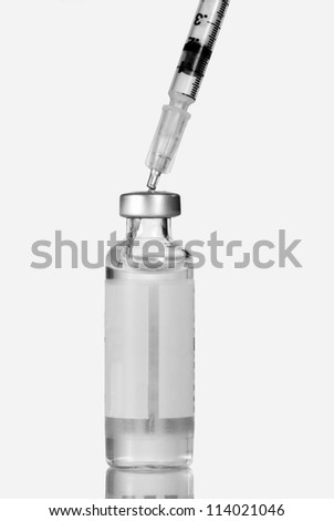 Closeup of a syringe injected into an insulin vial, bottle.  Isolated on white.