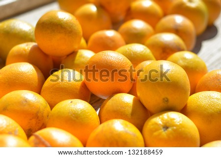 Closeup of a table full of valencia oranges at an outdoor fruit and vegetable stand.