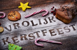 closeup of a table sprinkled with icing sugar or flour where you can read the text vrolijk kerstfeest, merry christmas in dutch, a rolling pin, some candy canes, a fruitcake and some christmas cookies