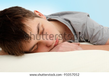 stock photo : Closeup of a teen boy sleeping on a bed