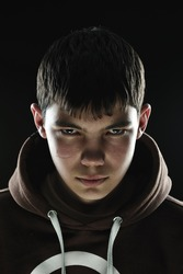 Closeup of a teenager with his hood down looking menacing