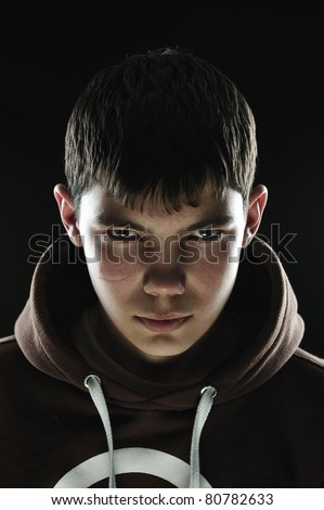 Closeup of a teenager with his hood down looking menacing