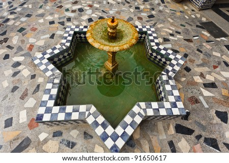 Closeup of a tiled fountain of geometric design in a courtyard in Morocco.