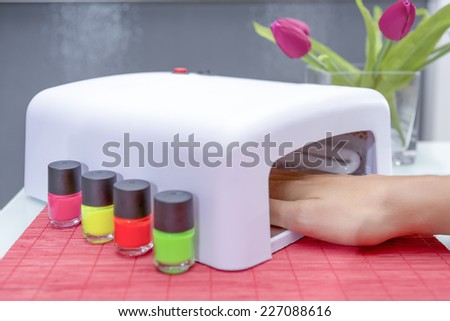closeup of a uv lamp with a female hand inside fixing the gel nail polish at the beauty salon