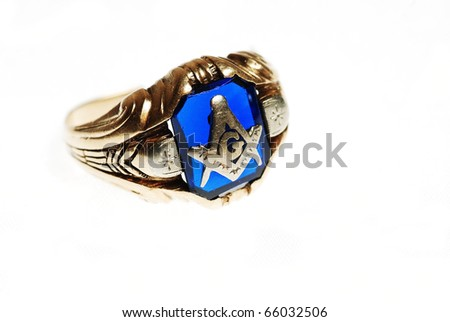 Closeup of a very old ring with masonic emblem on blue background, isolated on white background with light coming through the blue stone.