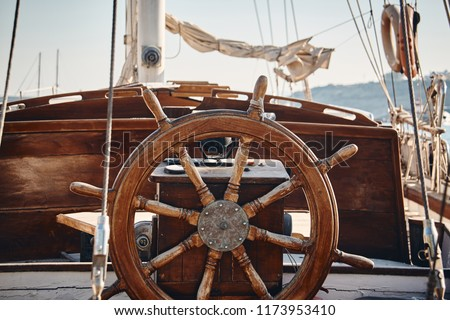 Closeup of a vintage hand wheel on a wooden sailing yacht. Yachting, helm of old wooden sailboat in port of sailing, rope, steering wheel, details of yacht.