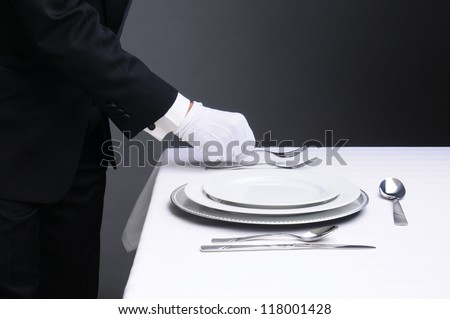 Closeup of a waiter in a tuxedo setting a formal dinner table. Horizontal format on a light to dark gray background. Man is unrecognizable.
