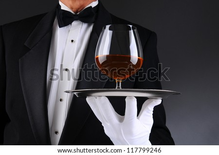 Closeup of a waiter wearing a tuxedo and holding a tray with a brandy snifter. Low angle man is unrecognizable. Horizontal format with a light to dark gray background.