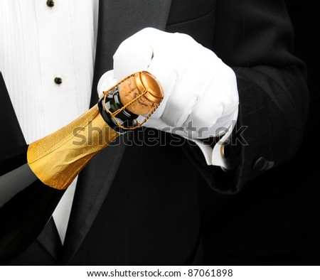Closeup of a waiter wearing a tuxedo opening a bottle of champagne. Hand bottle and torso only. Man is unrecognizable.