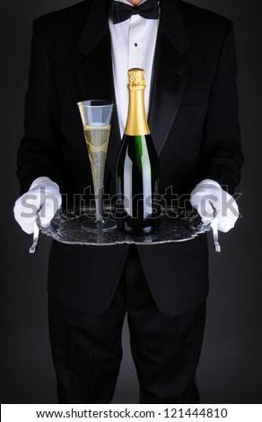 Closeup of a waiter with a bottle and flue of champagne on a silver serving tray. Vertical format over a light to dark gray background. Man is unrecognizable. - stock photo