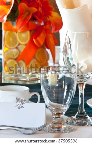 Closeup of a wedding table place setting with colorful centerpiece made up of sliced oranges in a vase with focus on the blank place card. - stock photo
