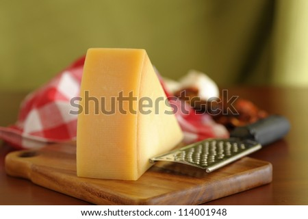 Closeup of a wedge of parmesan cheese on a wooden board.