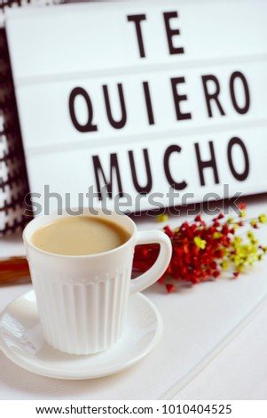 Shutterstock closeup of a white ceramic cup with coffee on a table, a bunch of flowers and a lightbox in the background with the text te quiero mucho, I love you so much written in spanish