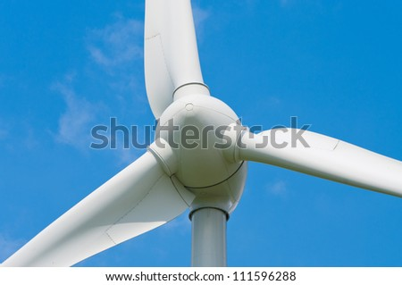 closeup of a wind turbine against a blue sky