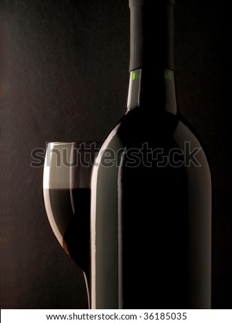 Closeup of a wine bottle and a wine glass on a black background.