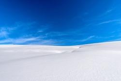 Closeup of a winter landscape with powder snow on blue sky with clouds. Lessinia Plateau (Altopiano della Lessinia), Regional Natural Park, Verona Province, Veneto, Italy, Europe.