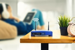 closeup of a wireless router and a man using smartphone on living room at home ofiice