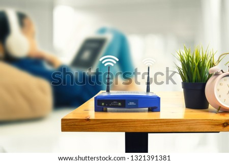 closeup of a wireless router and a man using smartphone on living room at home ofiice #1321391381