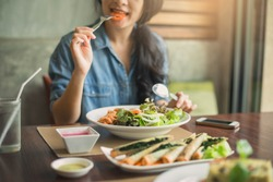 Closeup of a woman eating healthy salad . Beautiful smiling woman eating healthy salad.