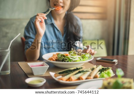 Closeup of a woman eating healthy salad . Beautiful smiling woman eating healthy salad.