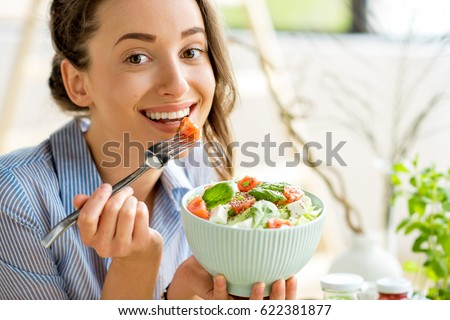 Closeup of a woman eating healthy salad with tomatoes cherry indoors