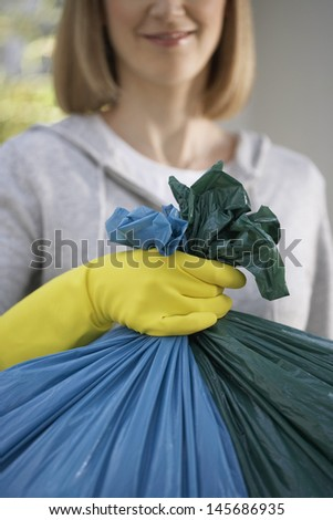 Closeup of a woman in rubber gloves holding garbage bag