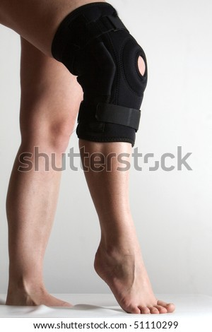 Closeup of a woman legs with one knee in a protective knee brace