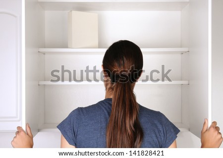 Closeup of a woman looking in an empty pantry. Seen from behind there is only one box of food. Horizontal format. - stock photo